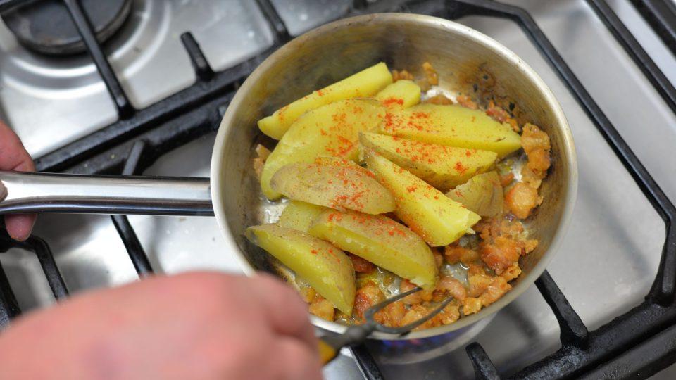 Na pánvi si rozpálíme sádlo se lžičkou kmínu, přihodíme na něj pokrájené vepřové škvarky a na ně nakrájené brambory