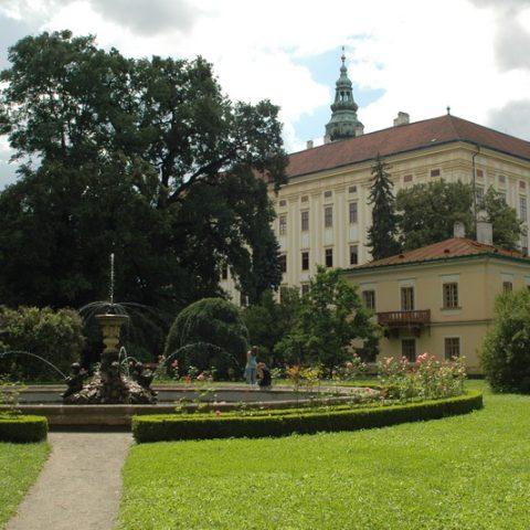 Pohled na Arcibiskupský zámek přes fontánu s vodní plochou a lekníny.